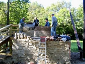 volunteers work on a firebox for this historic lime kiln