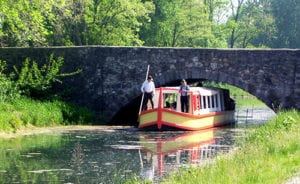 pass under a stone arch bridge in a canal boat