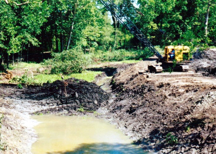 overgrowth and soil is removed to begin the canal restoration