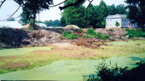 equipment removes overgrowth and soil to restore the canal
